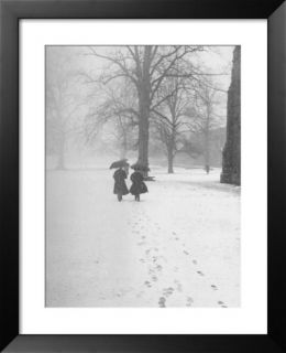 Snow Falling While People Take a Stroll Across Campus of Winchester College Pre made Frame