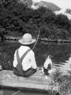 1920s 1930s Farm Boy Wearing Straw Hat And Overalls Sitting On Log With Spotted Dog Fishing In Pond Photographic Print by H. Armstrong Roberts