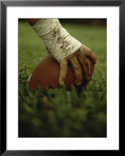 Close up of the Hand of an American Football Player Holding a Football Pre made Frame