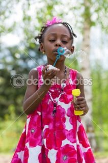 Cute african american little girl blowing soap bubbles  Foto stock